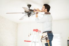 Handyman installing a ceiling fan royalty free stock images