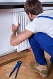 Handyman installing a radiator Stock Photo
