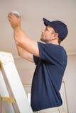 Handyman installing smoke detector Stock Image
