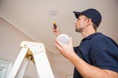 Handyman installing smoke detector Stock Photography