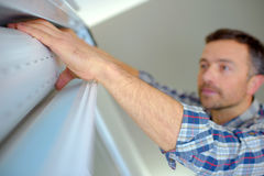 Handyman installing window shutter. Handyman installing a window shutter Stock Photography