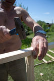 Handyman installing wooden flooring in patio, working with hammer Royalty Free Stock Images