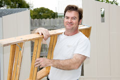 Handyman on the Job. Friendly handyman carrying a ladder and smiling Stock Photos