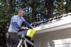 Handyman performing Home Maintenance -. Handyman on ladder clears leaf debris from eavestroughs before winter arrives Royalty Free Stock Photography