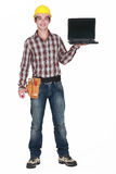 A handyman with a laptop. Royalty Free Stock Image
