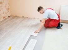 Handyman laying down laminate flooring boards. While renovating a house Stock Photo