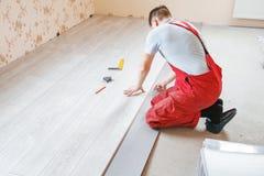 Handyman laying down laminate flooring boards. While renovating a house stock photos