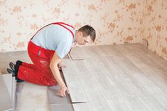 Handyman laying down laminate flooring boards. While renovating a house Royalty Free Stock Image