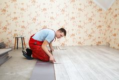 Handyman laying down laminate flooring boards. While renovating a house Royalty Free Stock Photography