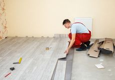 Handyman laying down laminate flooring boards. While renovating a house Royalty Free Stock Photo