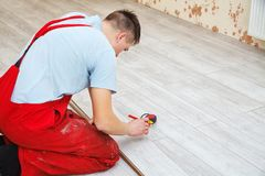Handyman laying down laminate flooring boards. While renovating a house Stock Images