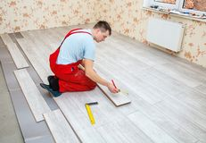 Handyman laying down laminate flooring boards. While renovating a house Royalty Free Stock Image