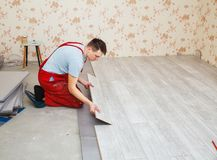 Handyman laying down laminate flooring boards. While renovating a house Stock Photos