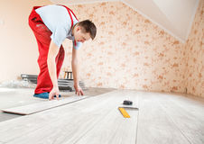 Handyman laying down laminate flooring boards Stock Image