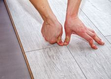 Handyman laying down laminate flooring boards. While renovating a house. hands closeup stock images