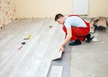 Handyman laying down laminate flooring boards. While renovating a house Stock Photo