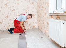 Handyman laying down laminate flooring boards Royalty Free Stock Photos
