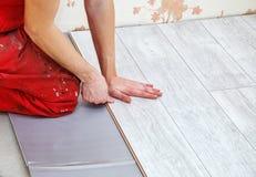 Handyman laying down laminate flooring boards. While renovating a house. hands closeup stock photos