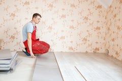 Handyman laying down laminate flooring boards Royalty Free Stock Image