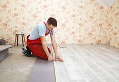 Handyman laying down laminate flooring boards. While renovating a house Stock Image