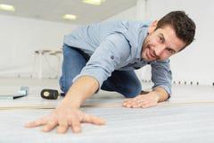 Handyman laying new flooring. Workman royalty free stock photo