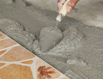 Handyman laying tile, trowel with mortar Stock Photos