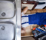 Handyman lies on the floor. And sink repairs stock photography