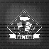 Handyman logo on  brick wall background in grey. Stock . Flat design Stock Photos