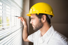 Handyman looking out the window Stock Photos