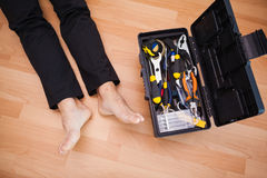 Handyman lying barefoot on floor with DIY tools Royalty Free Stock Photography