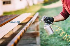 Handyman, male construction worker painting with spray gun on site royalty free stock photography