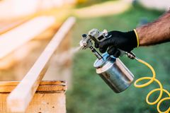 handyman, male construction worker painting wooden blocks, timber with spray gun on site royalty free stock photography