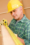 Handyman mature carpenter measure wooden beam Royalty Free Stock Image