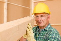 Handyman mature carpenter measure wooden beam Royalty Free Stock Images