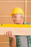 Handyman mature professional with spirit level Stock Photography