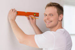 Handyman measuring wall. Cheerful craftsperson measuring the wall and looking at camera Royalty Free Stock Photography