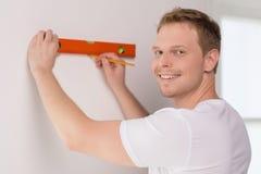 Handyman measuring wall. Cheerful craftsperson measuring the wall and looking at camera royalty free stock photography
