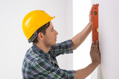 Handyman measuring wall. Confident craftsperson in hardhat measuring the wall level stock photography