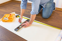 Handyman measuring wallpaper to cut Royalty Free Stock Photography