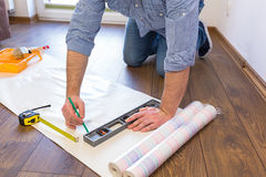 Handyman measuring wallpaper to cut. On the floor Royalty Free Stock Image