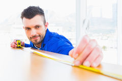 Handyman measuring wood board stock photography
