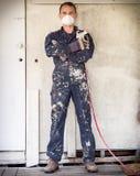 Handyman med målarfärgsprejaren arkivfoto