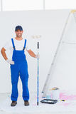 Handyman in overalls holding paint roller at home. Full length portrait of handyman in overalls holding paint roller at home Royalty Free Stock Photos