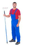 Handyman in overalls holding paint roller on white background Stock Image