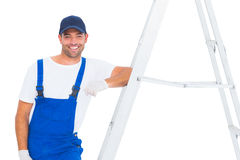 Handyman in overalls leaning on ladder Stock Images