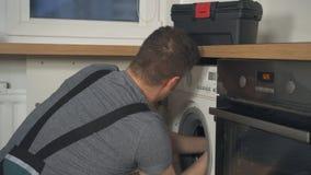Handyman in overalls repairing washing machine. Professional handyman in overalls repairing washing machine in the kitchen stock video footage