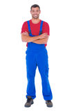 Handyman in overalls standing arms crossed over white backgound Royalty Free Stock Images