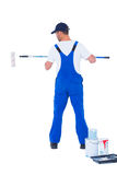 Handyman in overalls using paint roller on white background Royalty Free Stock Photography