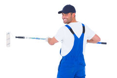 Handyman in overalls using paint roller on white background Royalty Free Stock Image