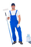 Handyman with paint roller standing by cans Royalty Free Stock Photos